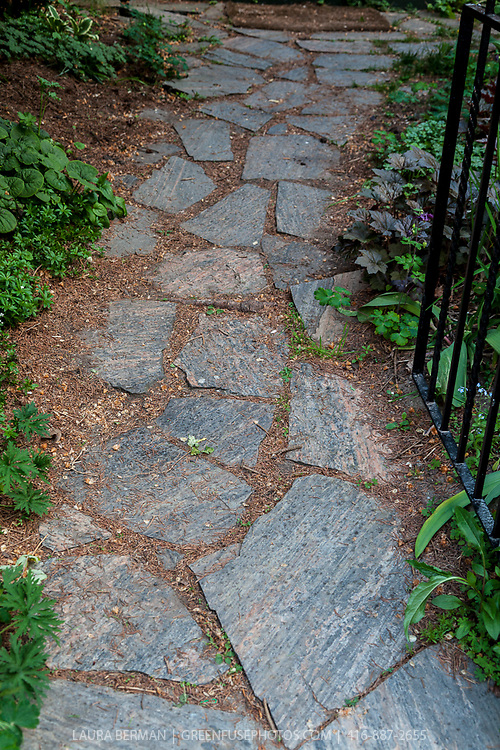 A garden path made from irregularly shaped pieces of flagstone forming 'crazy paving'.