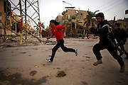 People have to run in order not to get shot by snipers on a so called sniper alley in Deir az-Zor. Residents of eastern syrian town Deir az-Zor joined arab spring protests against the regime of Bashar al-Assad from its early beginning in March 2011. Since summer 2012 the town with few hundred thousand inhabitants is embattled between the Syrian Army and different opposing rebel groups like Free Syrian Army and Jabhat al-Nusra. Deir az-Zor is target to constant shelling by artillery, war planes and short range missiles. Almost 70 percent of the town is rebel held while government forces remain in control over some residental areas and a strategic important airport. Deir az-Zor is widely damaged and some areas almost totally destroyed by fierce and long lasting battles. All direct road connections to Deir az-Zor are cut and fighters and returning residents as well depend on one provisional supply line across the Euphrates river which is regularly targeted by government snipers.