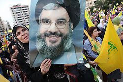 Supporters of the Shiite resistance and political group, Hizballah, rallied in the Dahiyeh southern suburbs of Beirut to watch a televised speech from Hizballah General Secretary Hassan Nasrallah. The rally was called for by Hizballah to celebrate Land Day, which is the 9th anniversary of Israel's withdrawal from southern Lebanon, which Hizballah and its supporters say was a victory over Israel. The rally comes just 13 days before Lebanese go to the polls to elect a new parliament. With Sunni Muslims and Shia Muslims mostly supporting their respective sectarian parties, Nasrallah praised Christian leader Michel Aoun. Aoun is head of the Free Patriotic Movement, which is allied with the Hizballah-led opposition March 8 coalition. ///A Hizballah supporter holds a poster of Hassan Nasrallah.
