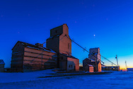 Venus, as an evening star in the western twilight of a December night, over the old Pioneer grain elevators at Mossleigh, Alberta. Lighting is fro the sky and partly from nearby streetlights.<br /> <br /> This is an HDR stack of 5 exposures, at 2/3rd stop increments from 1 second to 6 seconds, to preserve the dark foreground detail and bright sky. Merged with Adobe Camera Raw. A &ldquo;Misty Landscape&rdquo; filter from Luminar plug-in blended in to add the soft focus effect. Diffraction spikes on Venus added with Astronomy Tools action. With 24mm lens at f/5 and Nikon D750 at ISO 100.