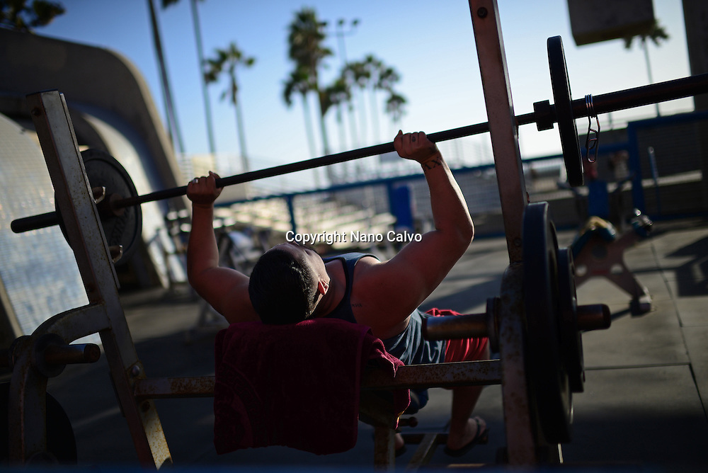 Man doing barbell bench press in outdoors gym at Venice beach, California.