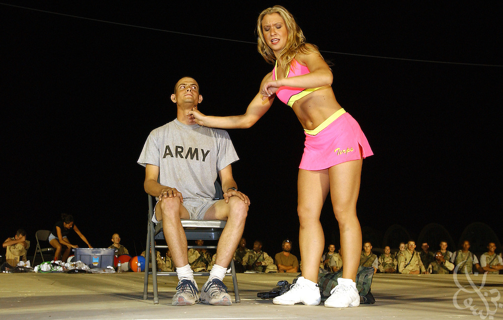 A cheerleader for the American football team the Baltimore Ravens jokingly checks the pulse of U.S. Army Sgt. Steven Jacob Waldon during a performance at the coalition forces'' Kandahar airfield May 08, 2002 in southern Afghanistan. The cheerleaders are visiting the airbase as part of a USO Tour for coalition forces deployed across the Middle East and Central Asia for Operation Enduring Freedom..