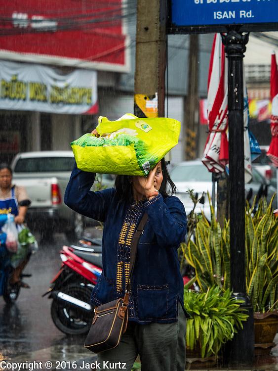 19 JANUARY 2016 - BURI RAM, BURI RAM, THAILAND: People duck raindrops during an unseasonal thunderstorm in Buri Ram, Thailand.    PHOTO BY JACK KURTZ