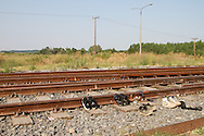 Migrants dry their shoes in the sun on the railway tracks outside the detention centre in Tychero. During the summer months it's possible for people to wade over the river into Greece. July 2011