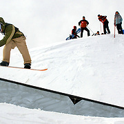 SHOT 12/14/2003 - The first stop of the Vans Triple Crown of Snowboarding wrapped up its first stop of the season with the Mountain Dew Pro Nationals Superpipe and Slopestyle Finals at Breckenridge, Co. Sunday. Some of the top names in snowboarding competed Friday through Sunday in three different events - Superpipe, Slopestyle and a Rail Jam. Patrick Kagi of Antrem, N.H. makes his way through the Slopestyle course and onto a rail as spectators watch from atop the superpipe Sunday. Kagi finished 23rd in the Slopestyle event..(Photo by Marc Piscotty/ © 2003)
