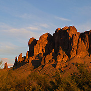 The rugged Superstition Mountains are reddened by the setting sun. The mountains, also known as the Superstitions, are located east of Phoenix, Arizona, and are involved in many superstitions. The legend of the Lost Dutchman's Gold Mine is centered in the range. Some Apaches also believe that the mountains contain a hole that leads to the lower world.
