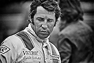 Mario Andretti paces around his Ferrari 312B2 during practice for the 1972 US Grand Prix in Watkins Glen, NY. He would finish sixth. Andretti was consumed with making the Ferrari faster despite having to use Firestone tires that were made for warmer temperatures and provided no grip in the cold weather. He had been keenly interested in expanding his career into Formula One since 1968, when he put Colin Chapman's Team Lotus 49 on the pole for his debut at the United States Grand Prix. <br /> <br /> He continued his search for the right combination of team and car in Formula One over the next four years with occasional races with Lotus, March, and Ferrari, while focusing his racing career efforts on his USAC, NASCAR and sports car commitments in the United States. Significantly, on his debut for Ferrari at the 1971 South African Grand Prix, he won his first Grand Prix matching that with a second victory three weeks later, at the non-championship Questor Grand Prix in the U.S. <br /> <br /> He would deliver on all of his promise when he re-teamed with Colin Chapman and Lotus in 1976, and go on to win the Formula One World Championship in 1978 in the ground-breaking Lotus 79.