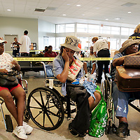 NEW ORLEANS, LA - September 4, 2005:  Evacuees from New Orleans were being flown to the city's airport via helicopter and unloaded on the tarmac. Unloaded on the tarmac in a scene similar to that of a war zone evacuation, they were then hustled from the helicopter onto waiting cargo carts ( normally used to move luggage) and rushed amid a throng of volunteers and into the airport where they received medical attention. Shortly after entering the airport, evacuees were screened and divided nto groups of 50 and told to go to a certain boarding gate. Evacuees only find out the destination of the flight, and their new temporary home, after boarding the flight. (Photo by Todd Bigelow/Aurora)..Elaine Chaney is visibly upset and consoled by her mother in law, Julia, before being evaluated by medical personnel inside the New Orleans Airport and then being flown to West Palm, Beach, Florida.......Members of the Chaney family, Kenneth (large man with straw hat), Anthony (other man with shorts), Elaine (younger woman), and Julia (woman with MLK prayer fan and hat--she's Ken's and Anthony's mother). Joseph (yellow shirt,using cane to walk) and Velma (red shorts and white ball cap). Joseph and Velma are Elaine's parents......