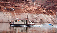 A houseboat moves along on Lake Powell.  Rental houseboats are one of the most popular ways to visit Lake Powell, and with the water level in the lake dropping steadily, there are more spite appearing where boats can stop.  Friday, March 14, 2003.