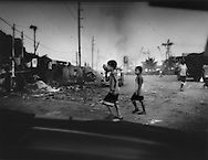 Squatter boys return to the new Smoky Mountain landfill site with a coconut to use as a ball for their game, Tondo Slum, Manila, Philippines.