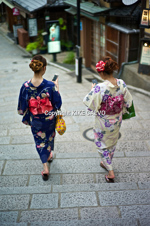 Asian women in traditional kimonos send text messages on their smart phones while exploring the stores and shops near the Kiyomizu Temple.