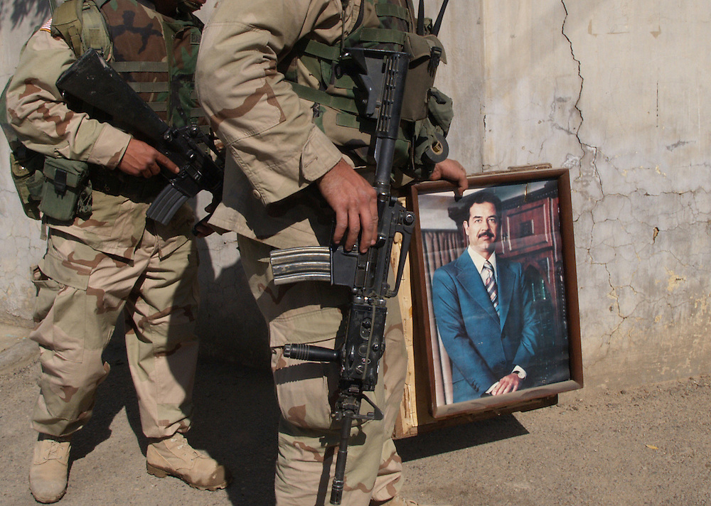 9 feb 2004..Baghdad, Iraq...US/ICDC Raid..As part of the ongoing training process the US forces accompany ICDC troops on a weapon search in a suburb of Baghdad...ICDC have recruited female soldiers. On raids they are able to placate the womenfolk of each household who are often both scared and offended by the intrusive seach by male troops....Whilst seaching for weapons the troops find framed portraits of former dictator Saddam. They confiscate these along with other documents linked to the regime.