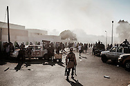 Libyan rebels  attack Bab Al Azizyia,  Gadhafi's headquarters compound in Tripoli. During and after the fighting, fighters later joined by civilians loot as many weapons they can carry from depots inside the compound. 23 August 2011.