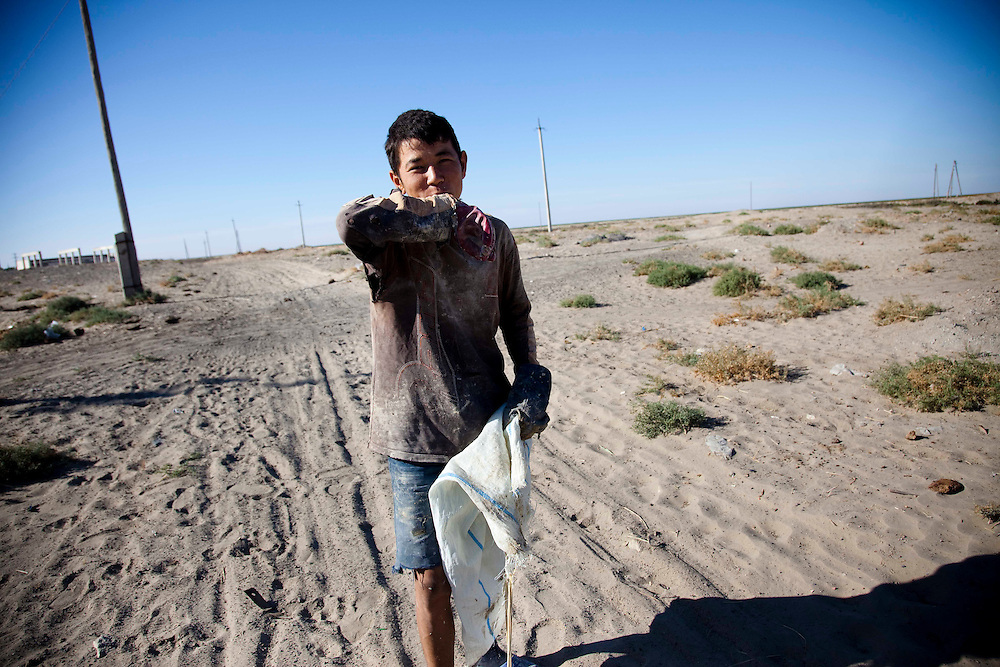 A worker tries to find something valuable from sands in Moynak, Uzbekistan