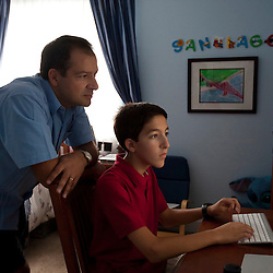 "Yago Gonzalez looks over the shoulder of son Santiago Gonzalez, 13, as he works on a computer project in his room, Littleton, Colo., Aug. 29, 2011. Santiago is a full-time college student at the Colorado School of Mines, an engineering university. He wakes up at 5:30 a.m. every morning during the academic semester to develop iPad and iPhone applications in a programming language called Objective C, which he learned from a textbook when he was 9 years old. That textbook and 86 similar volumes including Applied Finite Mathematics, Infinity in Your Pocket, Programming in C++ and Dictionary of Physics, sit in a glass-fronted bookcase opposite his bed. ""Exceptionally gifted"" is the commonly used phrase for kids as smart as Gonzalez."