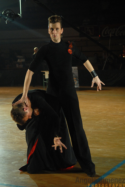 "World Champion same-sex ballroom dancers Robert Tristan Szelei, crouched, and Gergely Darabos, standing, compete in the latin category during the 2nd annual World Championship Same-Sex Ballroom Dancing competition, held in the dance couple's hometown, Budapest, Hungary, on October 21, 2006. ..Szelei and Darabos, who are known as the ""Black Swans,"" are the reigning world champions in men?s Latin same-sex ballroom dancing. They have been training and preparing to host the 2nd annual World Championship and the Csardas Cup, the first-ever Eastern European same-sex ballroom competition, both held at the Korcsarnok arena.  This is the pinnacle event of the blossoming same-sex ballroom scene...Szelei and Darabos went on to win the men?s Standard division and finished fourth in the Latin division. ..The event was organized by the US-based World Federation of Same-Sex Dancing, which hosted the first World Championship Same-Sex championships in 2005 in Sacramento, California. The Black Swans did a large amount of the coordination and planning in Budapest, a city that had never seen an event of this kind. When government funding fell through, they secured funding from patron Desire (accent on the ?e?) Dubounet, owner of the local Club Bohemian Alibi drag club. ..The World Championship events are newly recognized, but same-sex dancers have been competing on a national and international circuit for a number of years, especially in Europe, including at the Eurogames, the Gay Games, the London Pink Jukebox Trophy and the Berlin Open, among others. Countries including the United States, the Netherlands, Germany and, now, Hungary, hold their own national same-sex championships. Hungary held its first national championships in April 2006...Szelei and Darabos spent three months at the Sacramento Dancesport same-sex dance school in California this summer, on the first scholarship offered by the World Federation. The men both got their early training as opposite sex dancers, then starte"