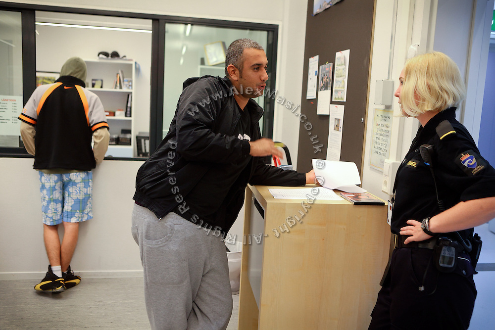 An inmate (centre) is talking to a woman guard (right) inside the prison library, containing not only books but also magazines, CDs and DVDs, inside the luxurious Halden Fengsel, (prison) near Oslo, Norway.