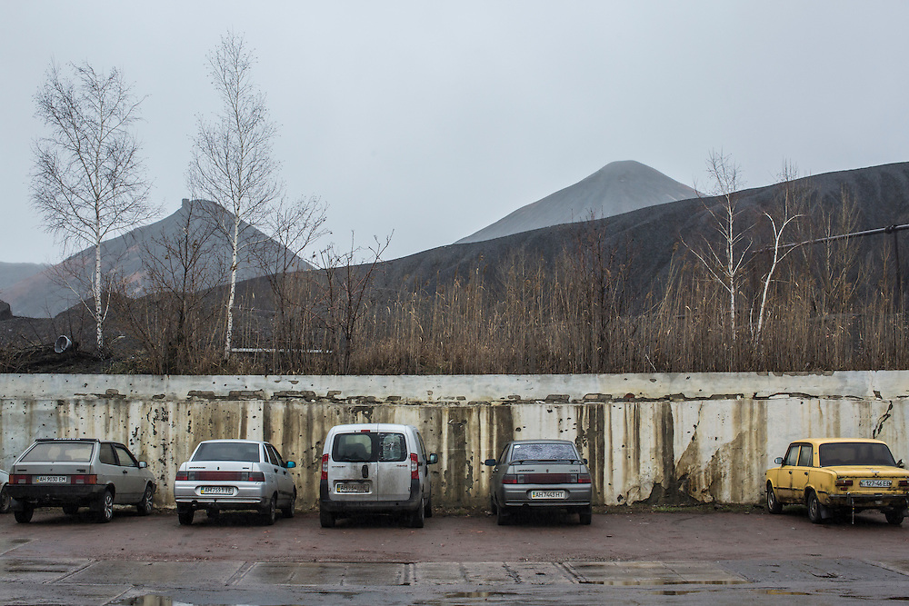 Piles of mine tailings tower over a parking lot at the Shcheglovskaya Coal Mine on Friday, March 25, 2016 in Makiivka, Ukraine.