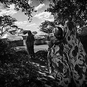 Mariamou, 16 ans, se dirige vers la tente de son père avec son fils et sa soeur, le 10 décembre 2014 dans le camp de réfugiés centrafricains de Gado, à l'est du Cameroun. Mariée de force deux ans auparavant, Mariamou a dû abandonner l'école. Les mariages précoces et forcés sont en constante augmentation dans les camps. On constate même de plus en plus de mariages entre différents groupes ethniques, ce qui était très rares en Centrafrique.