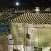 "A detainee looks out from the fence surrounding his cell in Camp 4 at the detention facility in Guantanamo Bay, Cuba. Camp 4 is a communal style camp where more compliant detainees live in small groups and have access to a more open air environment. Approximately 250 ""unlawful enemy combatants"" captured since the September 11, attacks on the United States continue to be held at the detention facility.(Image reviewed by military official prior to transmission)."
