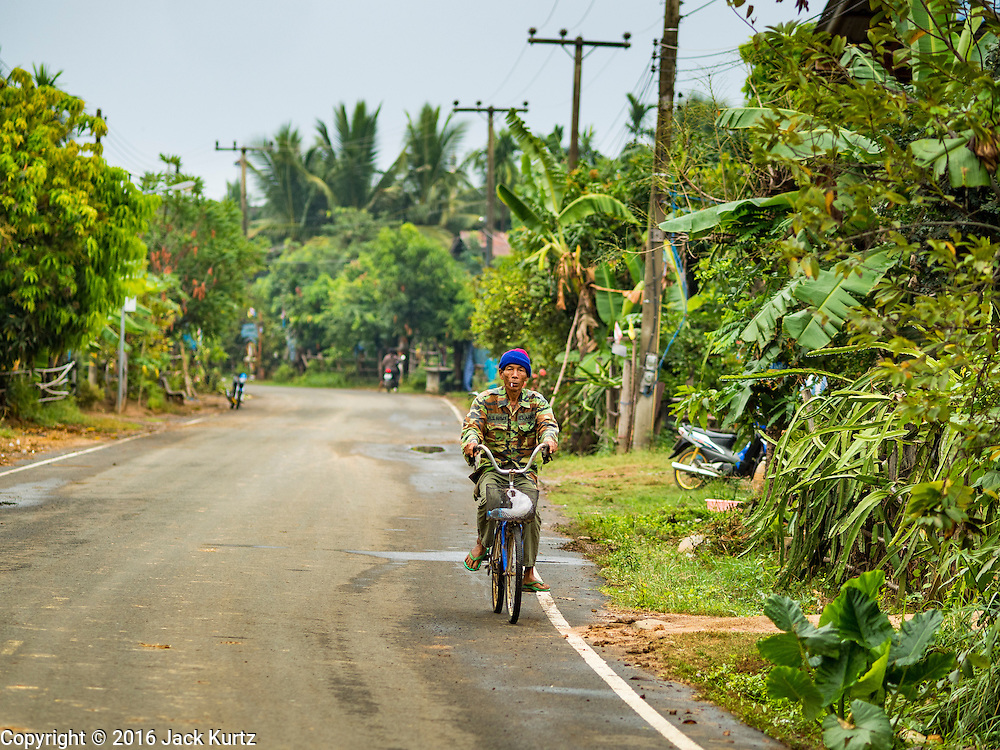 20 JANUARY 2016 - SI LIAM, BURI RAM, THAILAND:  A man rides his bicycle down the main road in Si Liam, Buri Ram. The drought gripping Thailand was not broken during the rainy season. Because of the Pacific El Nino weather pattern, the rainy season was lighter than usual and many communities in Thailand, especially in northeastern and central Thailand, are still in drought like conditions. Some communities, like Si Liam, in Buri Ram, are running out of water for domestic consumption and residents are traveling miles every day to get water or they buy to from water trucks that occasionally come to the community. The Thai government has told farmers that can't plant a second rice crop (Thai farmers usually get two rice crops a year from their paddies). The government is also considering diverting water from the Mekong and Salaween Rivers, on Thailand's borders to meet domestic needs but Thailand's downstream neighbors object to that because it could leave them short of water.       PHOTO BY JACK KURTZ