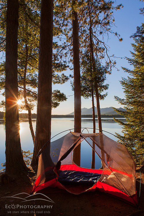 A tent at sunrise on Flagstaff Lake in Eustis, Maine. Bigelow Mountain is in the distance.