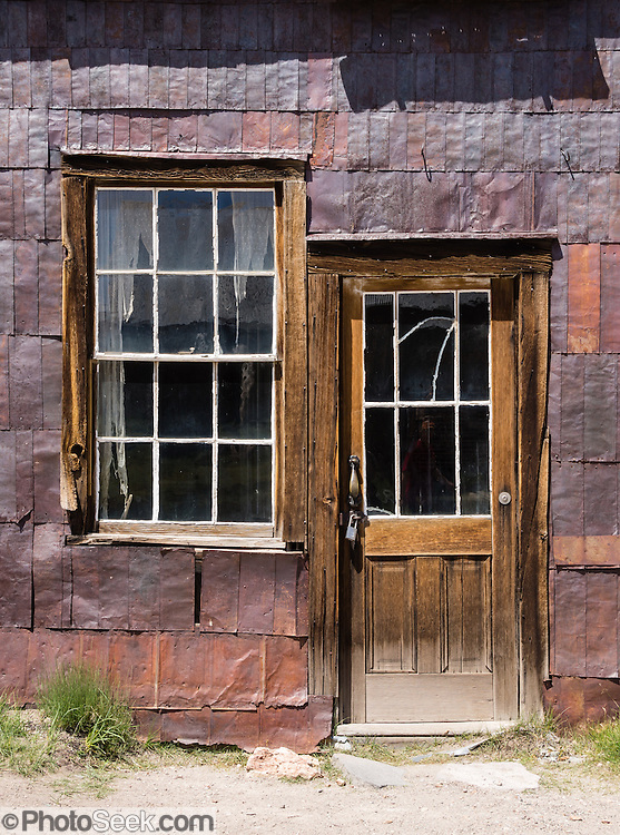 """Rusty iron siding frames a window & door at Bodie, California's official state gold rush ghost town. Bodie State Historic Park lies in the Bodie Hills east of the Sierra Nevada mountain range in Mono County, near Bridgeport, California, USA. After W. S. Bodey's original gold discovery in 1859, profitable gold ore discoveries in 1876 and 1878 transformed """"Bodie"""" from an isolated mining camp to a Wild West boomtown. By 1879, Bodie had a population of 5000-7000 people with 2000 buildings. At its peak, 65 saloons lined Main Street, which was a mile long. Bodie declined rapidly 1912-1917 and the last mine closed in 1942. Bodie became a National Historic Landmark in 1961 and Bodie State Historic Park in 1962."""