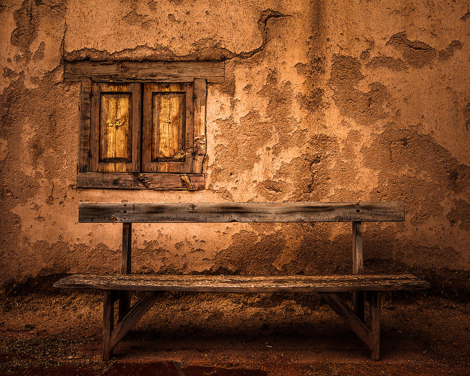 An old wooden bench in front of an adobe wall in Taos, New Mexico.