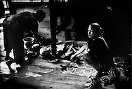 Ruthann, Philippus's wife, working in the kitchen of their raised house, Long Kelamu, Sarawak, Malaysia.  One or two generations ago, Penan did not live such a settled semi-nomadic existence.  Instead they roamed the rainforest following game or fruit that was in season.  This is no longer possible because selective logging has pulled out important trees, damaged the soil, silts up rivers reducing food for the Penan, fish in streams and prey animals on the forest floor and in the canopy.  Now, they can no longer sustain themselves from the forest alone and suppliment their diet with rice bought from the nearest towns, like Long Lellang.    According to the United Nations Environment Programme - World Conservation Monitoring Centre (UNEP-WCMC), 2004 World Database on Protected Areas Malaysia lost an average of 78,500 hectares of forest per year between 1990 and 2000.   Between 2000 and 2005, the rate of deforestation actually increased by 85.1%.  From 1990 to 2005, Malaysia forest cover decreased by 1.5 million hectares.