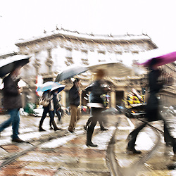 Intentionally motion blurred abstract image of commuters in a european city in a rainy day. Shot in Milan, Italy