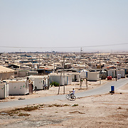 A boy bikes through the sea of caravans in Zaatari camp for Syrian refugees in Jordan. The camp initially opened in July 2012 as a temporary solution to the influx of Syrian refugees. With no end in sight to the war, tents gradually were replaced with caravans, a more protective shelter from the harsh desert environment. However, the caravans are essentially metal boxes, which leak in the winter and are suffocating in the brutal summer heat. Of the 665,000 registered Syrian refugees in Jordan, 80,000 reside in Zaatari camp.