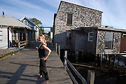 Claudia Steinberg (in front of their house on the right) and Barbara Epler bought this wooden house in Jamaica Bay, Rockaway, and turned it into an artful weekend escape.<br /> Rockaway Beach, Queens, New York, USA..Rockaway is making a comeback for New Yorkers who share the endless beach with the locals on weekends. Rockaway Beach is  also one of the favorite spots for surfers on the East Coast, a stretch of the beach is reserved exclusively for them. <br /> Rockaway Beach, Queens, New York, USA, <br /> <br /> Photo &copy; Stefan Falke<br /> www.stefanfalke.com<br /> stefanfalke@mac.com<br /> 917-2149029