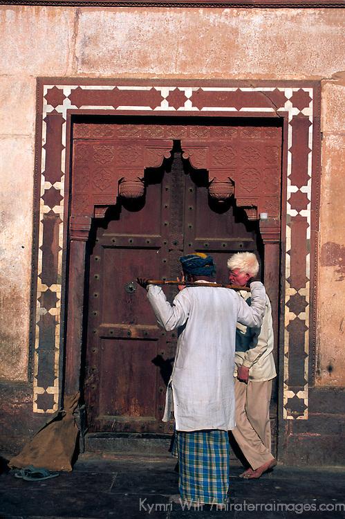 Asia, India, Uttar Pradesh, Fatehpur Sikri. Two men at one of the gates of Fatehpur Sikri.