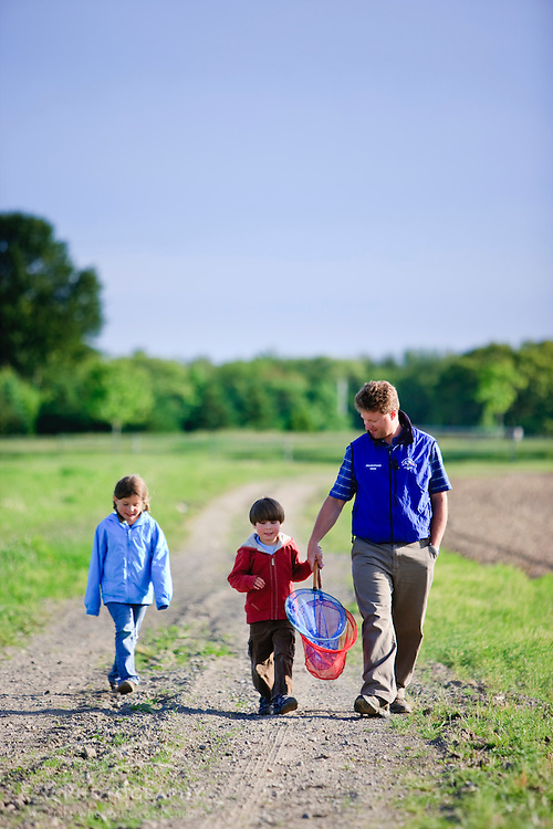 A man and his two children walking on a farm in Ipswich, Massachusetts.