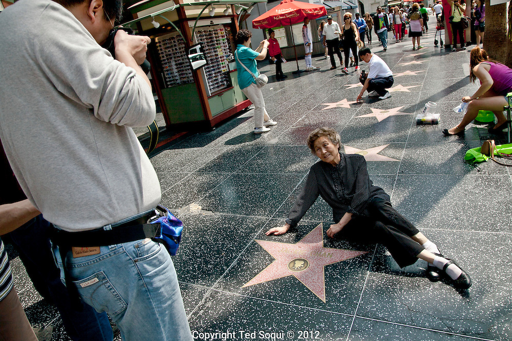 A tourist lays next to Jackie Chan's star on Hollywood's Walk of Fame.