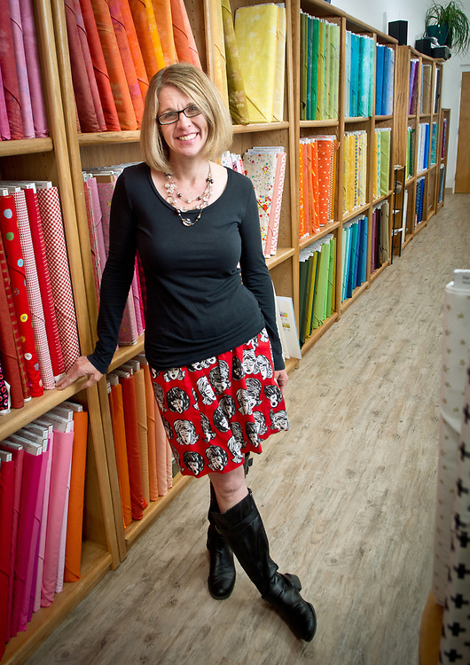 mkb032917/metro/Marla Brose --  Suzanne Kelly, one of the owners of Hip Stitch, leans again a wall of fabric inside the quilt shop's new location at 2320 Wisconsin St. NE in Albuquerque, N.M.  (Marla Brose/Albuquerque Journal)