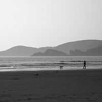 Europe, United Kingdom, Wales. Person and dog at Newgale Beach in Pembrokeshire.