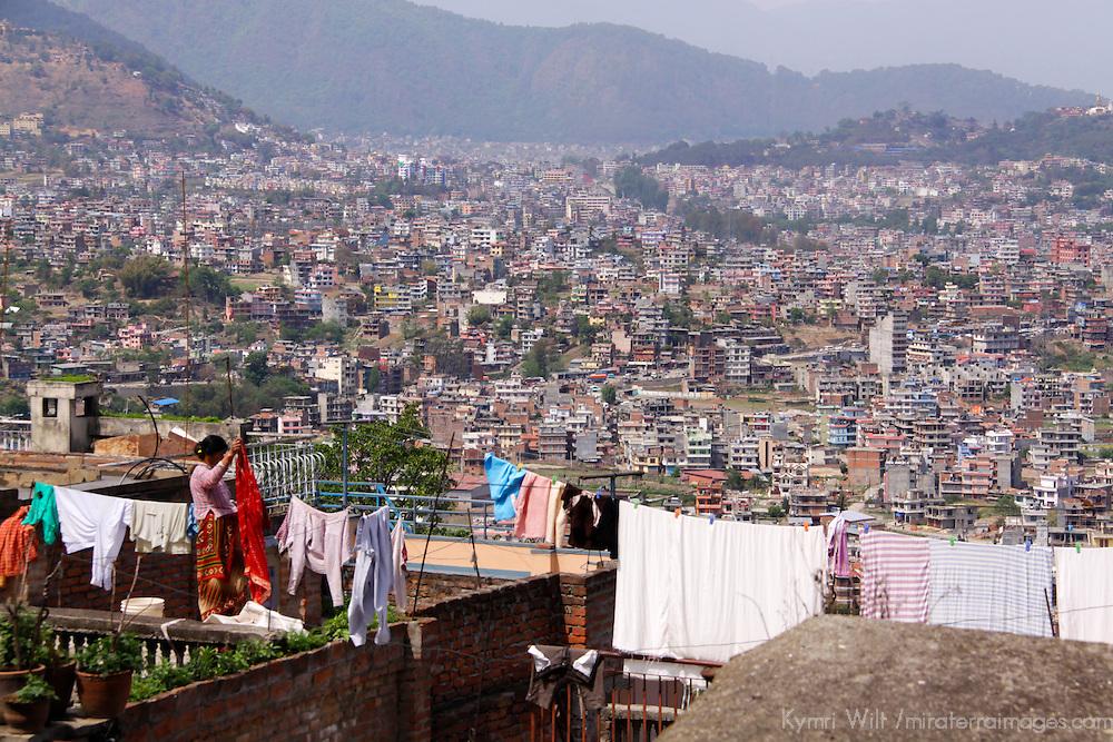 Asia, Nepal, Kathmandu. Nepali woman hanging laundry overlooking Kathmandu cityscape.