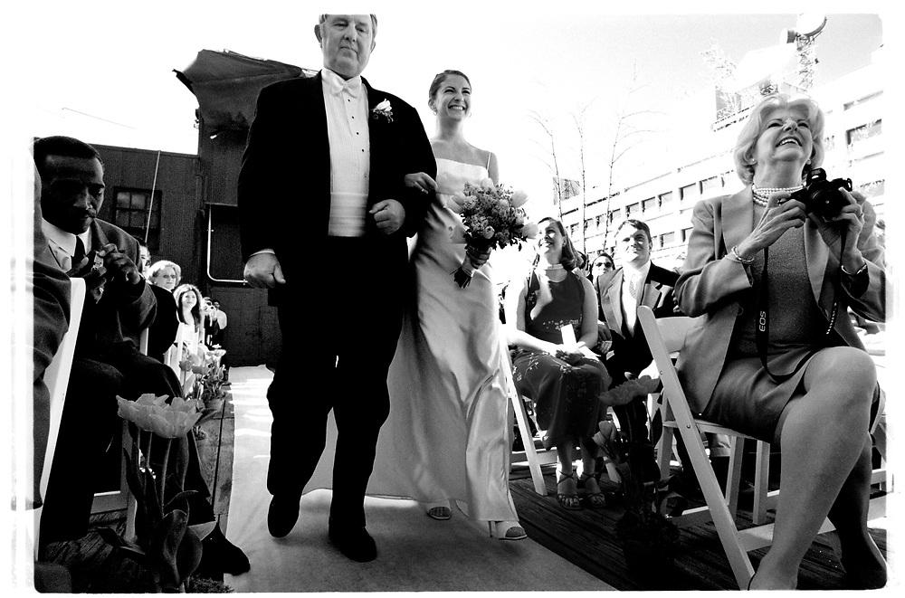 Ut ur varuhissen och uppför mittgången på byggnadens tak leds Tory fram till altaret av sin styvfar förbi tårögda släktingar vänner och mor..Joby Harold and Tory Tunnell's wedding in New York City..Photographer: Chris Maluszynski /MOMENT