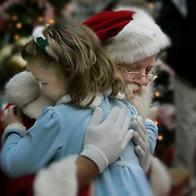 Santa and child embrace.