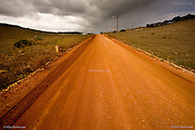 Almost a dirt track, this red dusty road cuts through dry grass covered hillsides near Figueira near the Algarve coast. Dark clouds loom on the horizon from approaching stormy weather