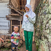CAPTION: Dwi plays with her younger brother at their home in Bandar Lampung. She is eager to put into practice what she has learned about climate change at school, so she's installed a number of biopores outside their house and has started collecting organic waste to make compost. LOCATION: Dwi Wijayanti's house, Jl. St. Badaruddin II No 56, Bandar Lampung, Indonesia. INDIVIDUAL(S) PHOTOGRAPHED: Dwi Wijayanti and her younger brother Muhammad.