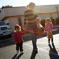 LEHIGH ACRES, FL -- January 23, 2009 -- Megan Brown of Lehigh Acres walks with her daughters Kayley, 2, left, and Sydney, 4, after picking up free bread and pastries for her family at the bread line at Faith Lutheran Church in Lehigh Acres, Fla., on Friday, January 23, 2009.  Lehigh Acres has become a symbol for the fallen American Dream - with only two years separating itself from housing market boomtown to a current landscape of abandoned developments and struggling businesses.