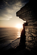 The sun sets over the Indian Ocean near Uluwatu Temple, Bali, Indonesia.