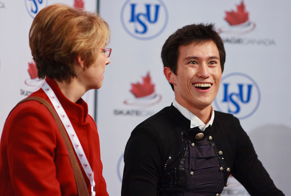 20101030 -- Kingston, Ontario -- Gold medalist Patrick Chan of Canada awaits his marks with his coach Christy Krall following his free skate at Skate Canada International in Kingston, Ontario, Canada, October 30, 2010. <br /> AFP PHOTO/Geoff Robins