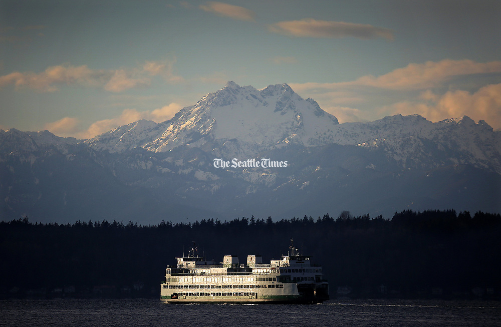 "A Washington State Ferry cruises past the Olympic Mountains peak ""The Brothers,"" as chilly temperatures in the 30s contrast with warm light in Seattle. (Ken Lambert / The Seattle Times)"