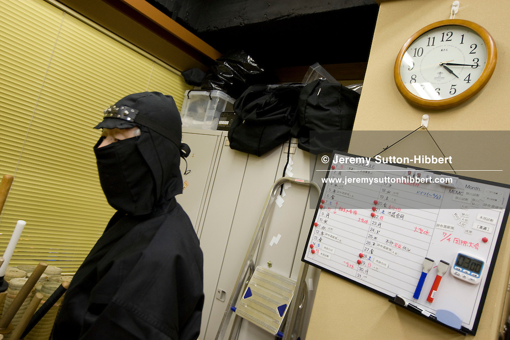 A modern day ninja beside a noticeboard, from the Keizan group, in the Keizankai Dojo, in Ikebukuro district of Tokyo, Japan, Wednesday, March 25, 2009.