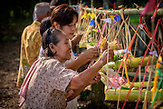 Local women hang offering baskets made of banana trees, at a village home blessing and merit making ceremony in Nakhon Nayok, ‎Thailand