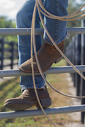detail of cowboy boots and a lasso on a metal fence