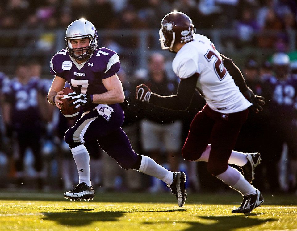 University of Western Mustangs quarterback Donnie Marshall scrambles to avoid a tackle by Byron Metcalfe of the McMaster  Marauders during the Mustang's 34-28 victory over the Marauders in the OUA semi-Final at TD Waterhouse Stadium in London, Ontario, November 6, 2010.<br /> <br /> The Canadian Press/GEOFF ROBINS